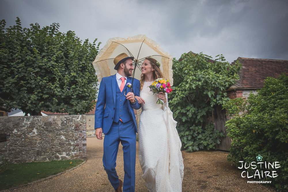 Umbrella wedding in the rain Grittenham barn