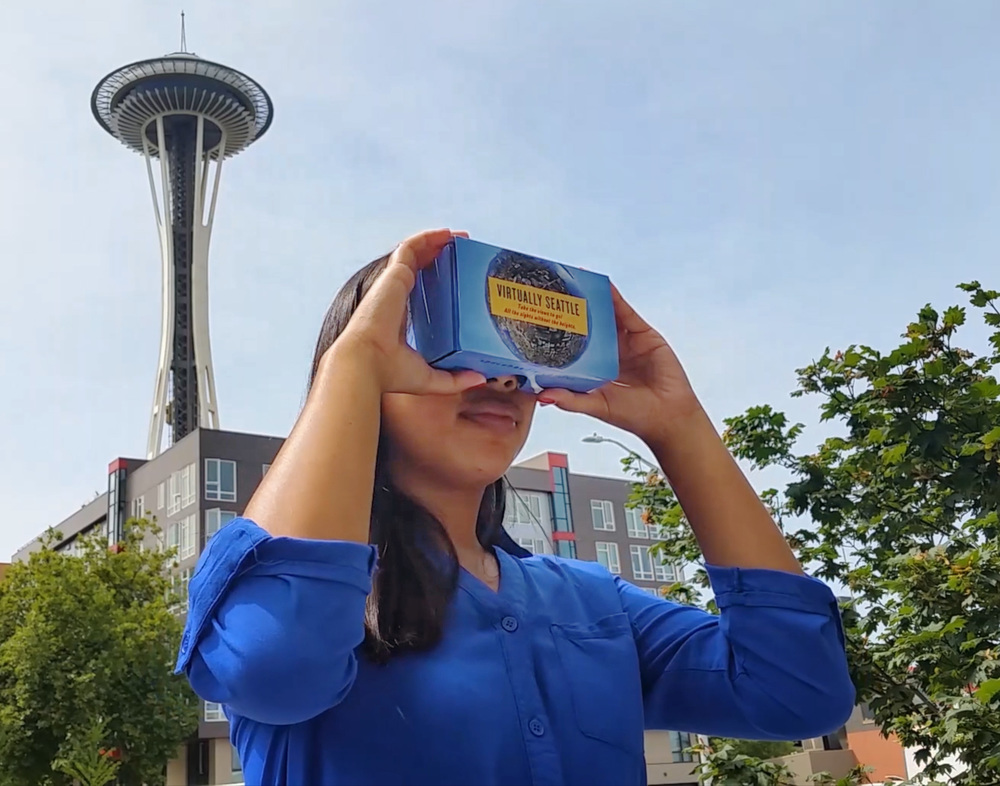 "A visitor enjoying the SPACE NEEDLE 360º in the Space Needle ""Virtually Seattle"" Cardboard VR headset."
