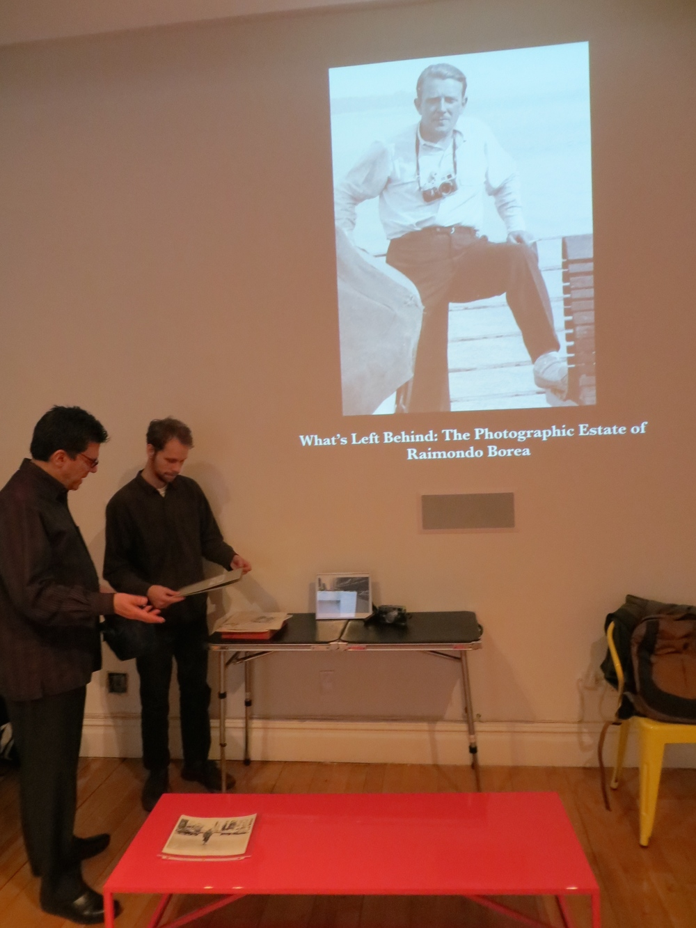 David Deitch and Alex Westhelle handling original photos and documents from the estate of photographer Raimondo Borea.
