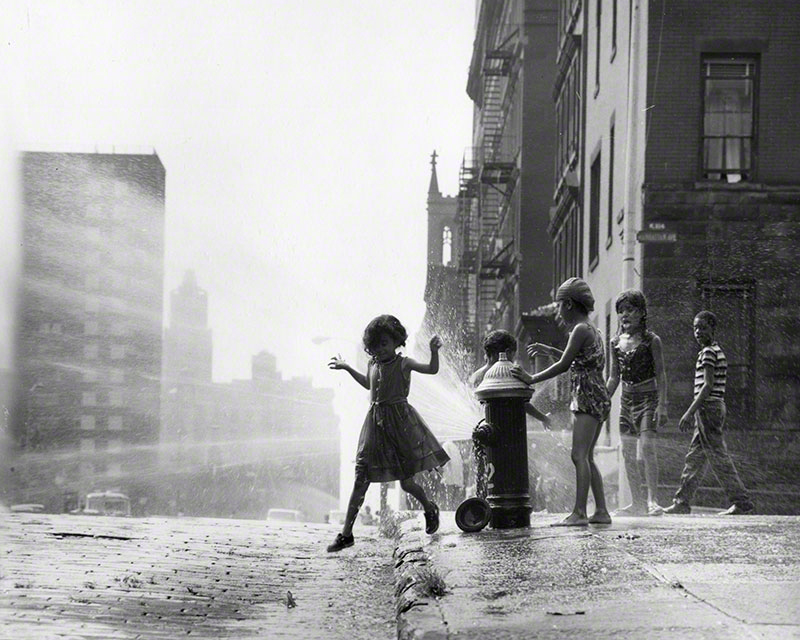 Children playing in the spray of an open hydrant; looking west towards the corner of 104th and Manhattan Ave.