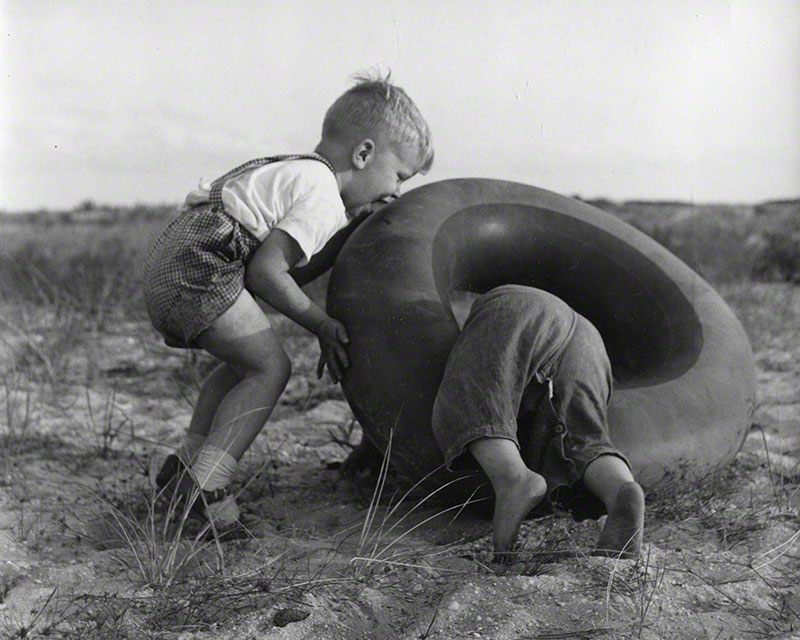 Roberto and another child playing with an inner tube