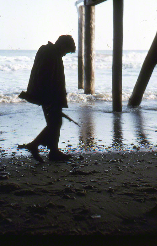 Silhouette of Roberto holding a rifle and walking under a pier