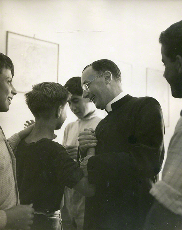 Close-up of Msgr. Carroll-Abbing in conversation with a group of boys