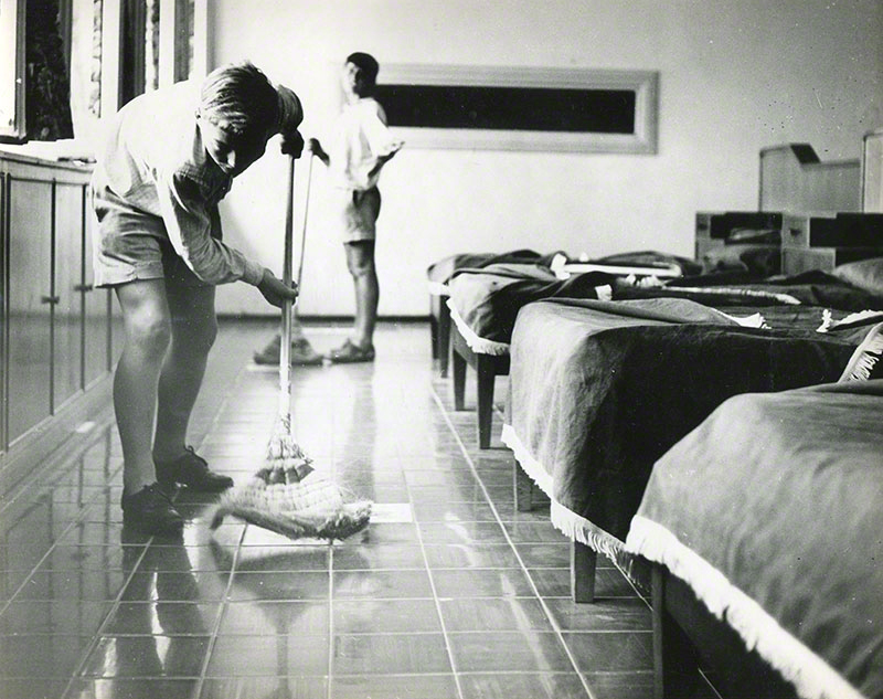 Two boys polishing the floor of a dormitory room