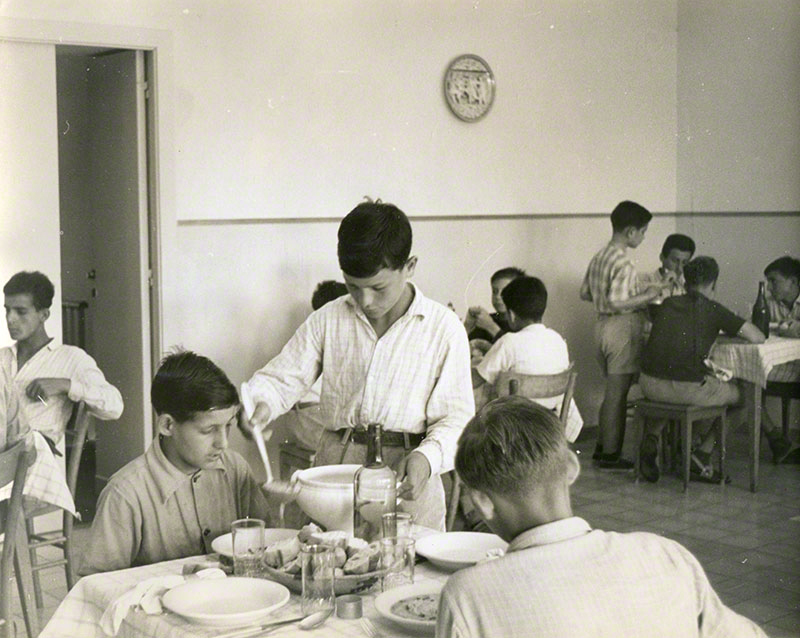 Dining hall scene; central focus on boy ladling soup