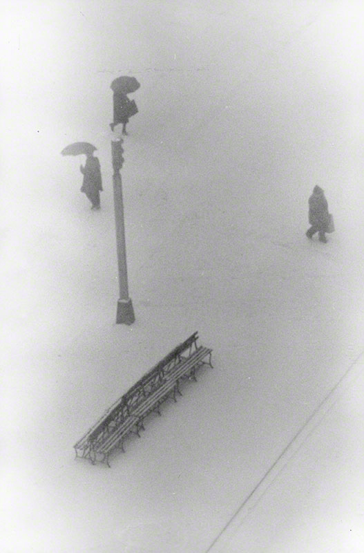 Three unassociated pedestrians on  snow covered traffic island, walking in opposite directions; as viewed from above