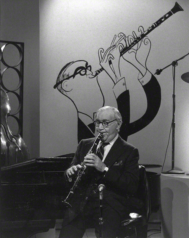 Goodman playing clarinet; background is a Hirshfeld illustration of him playing clarinet