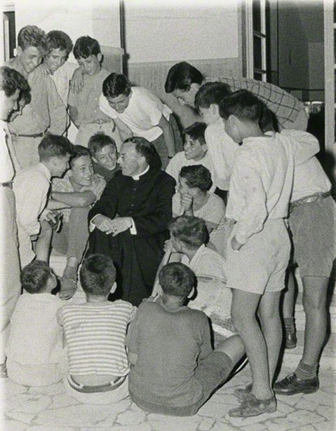Soft focus photo of a group of smiling boys surrounding Msgr. Carroll-Abbing