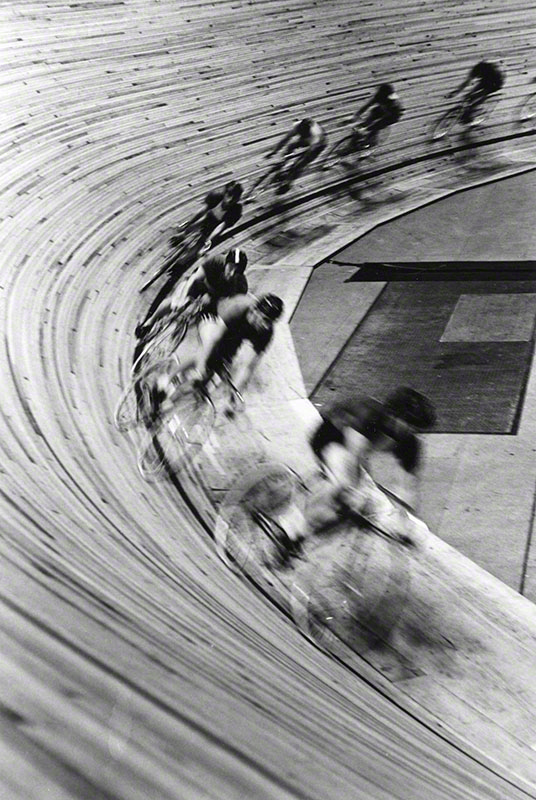 Blurred image of oncoming speed cyclists on indoor wooden track