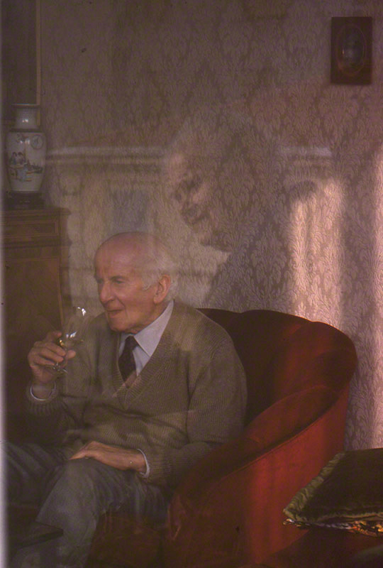 Elderly gentleman seated holding a glass of wine; the face of an elderly woman is overlaid on image