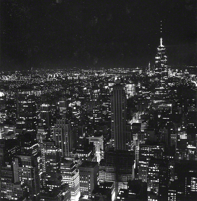 Nighttime aerial view of off-center Empire State Building and surrounding buildings; high contrast