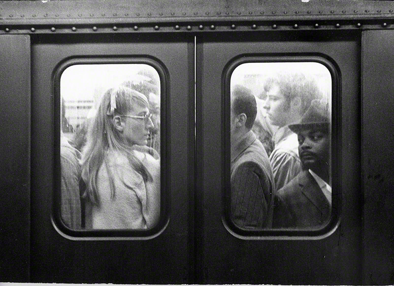 Passengers on a crowded train as seen through the windows of the door