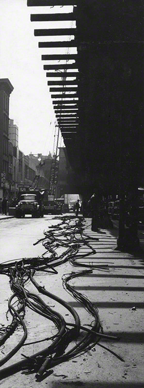 High contrast long view from street level of the [dismantling] of the Third Ave. El; the street is covered with cables
