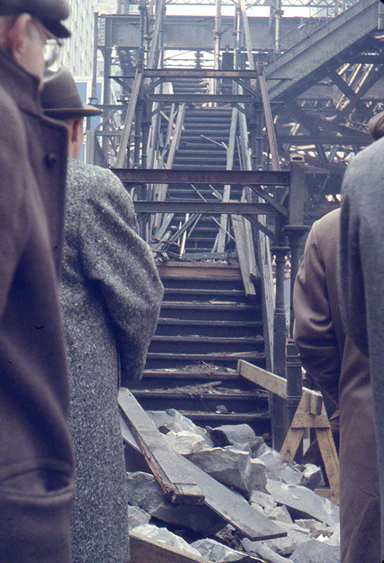 Looking up staircase of Elevated littered with debris; group of gentlemen in foreground