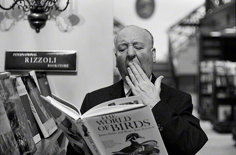 "Alfred Hitchcock yawning while perusing a book entitled ""The World of Birds"" (ca. 1963)"