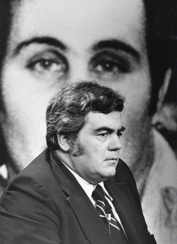 Jimmy Breslin; background blow-up photo of Son of Sam