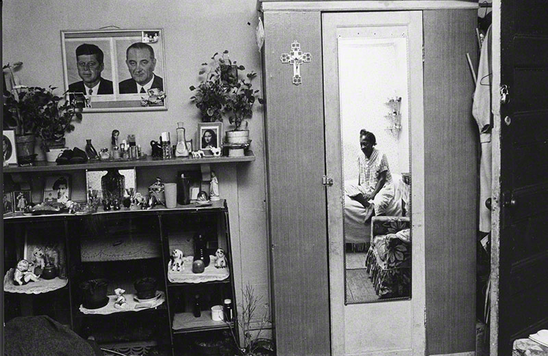 African American women seated on bed, reflected in door mirror ; displayed  on side wall mantel and shelves are knickknacks and photos; prominent photographs of JFK and LBJ hanging above on wall