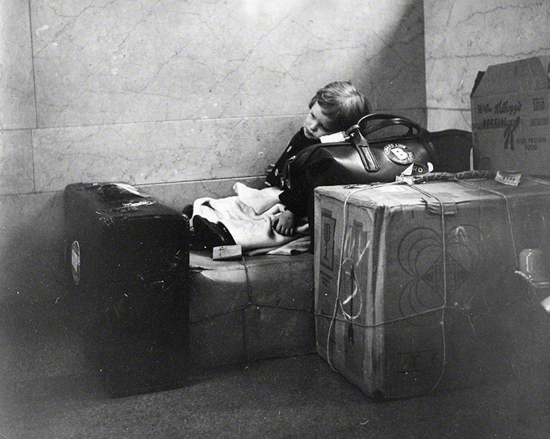 Little girl resting on suitcases and boxes