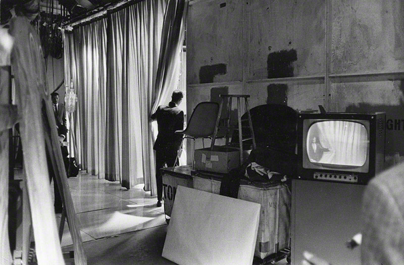 Long shot of Carson from behind; this image is captured back stage while he is parting the curtains before coming on stage; the reverse angle shot can be seen on a tv monitor.