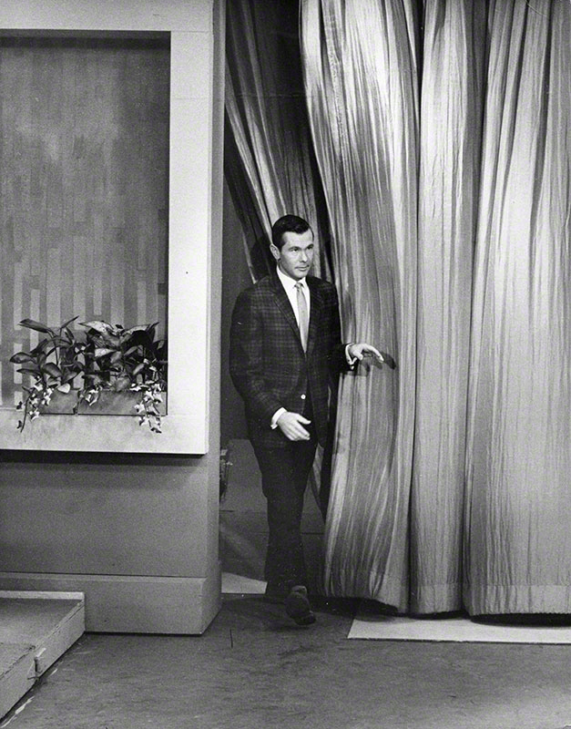 Carson entering stage through curtains