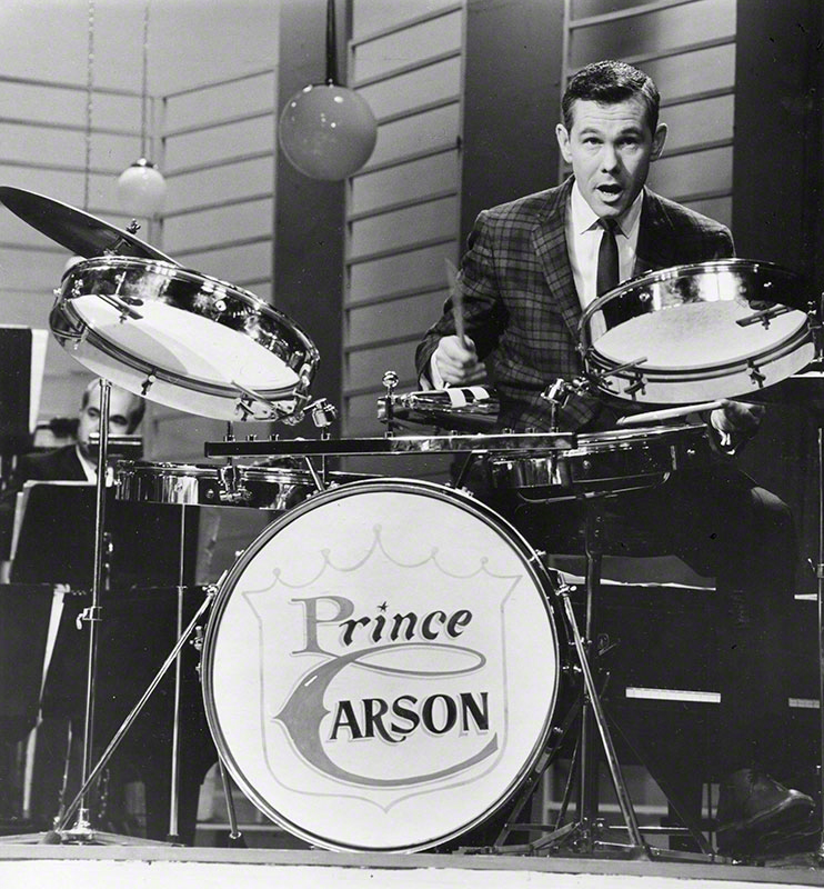 Close-up of Carson playing drums with the band.
