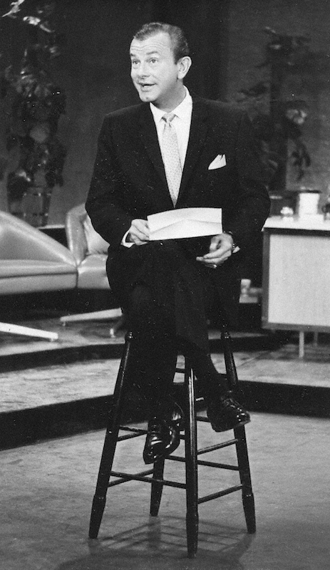 Paar delivering a monologue while sitting on a stool holding an envelope.