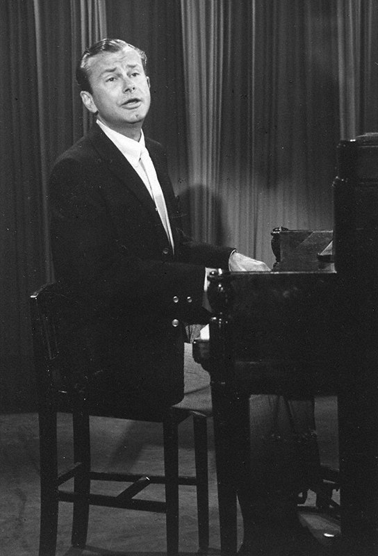 Close-up of Paar playing the piano and singing.
