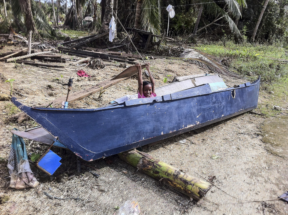 A Veloso girl plays in one of the many damaged fishing boats in town.  Typhoon Haiyan not only destroyed houses and crops, it left many of the region's fishermen without viable means of income.
