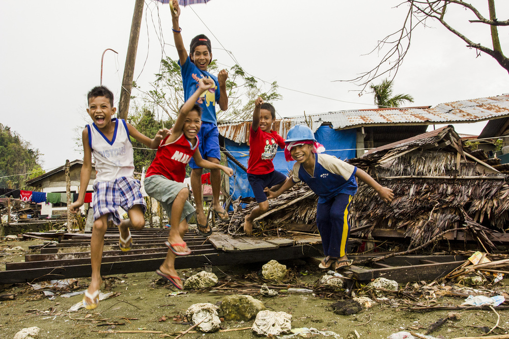 Boys jump from the flattened remains of a seaside house in their village, Veloso, in Samar.