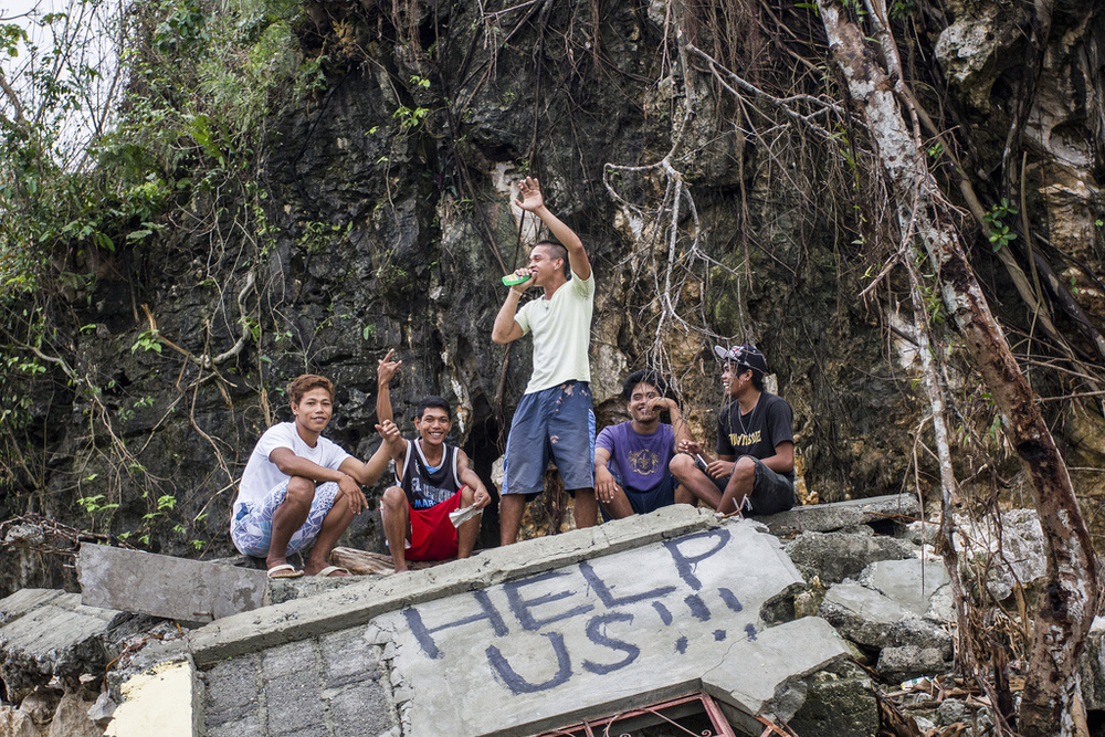 Young men in Legaspi, Samar, hang out atop the wreckage of a concrete house. Behind them stands one of the many rock formations in the region that saved hundreds of families from the six metre storm surge of Typhoon Haiyan.