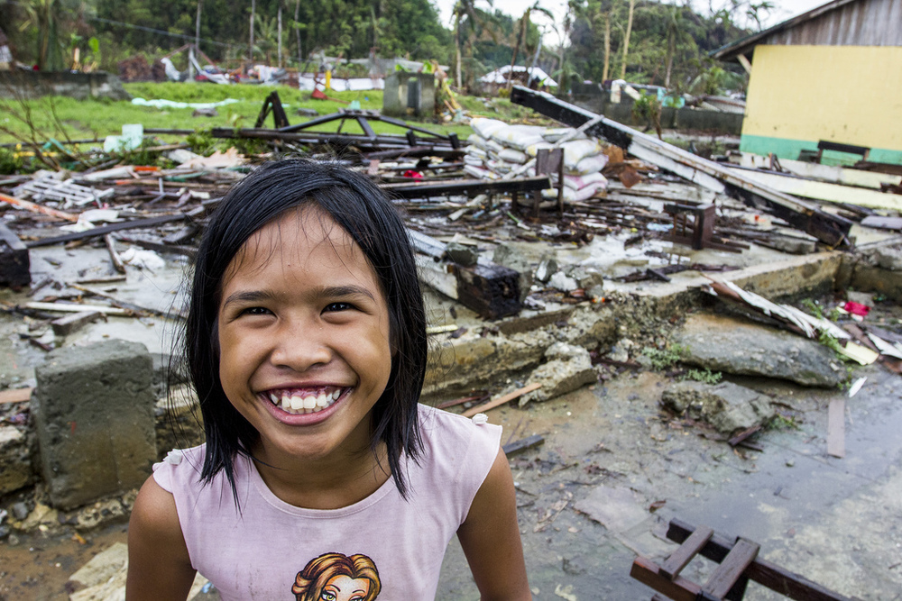 A grinning girl in front of one of the school buildings razed by Typhoon Haiyan in Veloso, Samar.