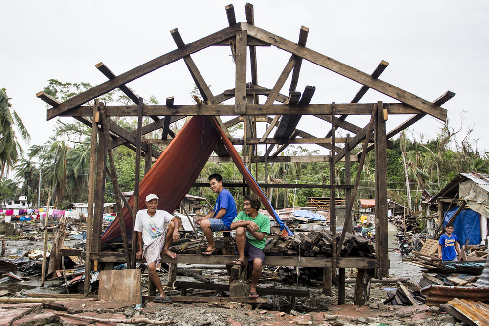 Men taking a break from their construction work under an aid tarp.  Lack of strict building codes and simple house designs mean that many houses destroyed by Typhoon Haiyan can be rebuilt fairly quickly.