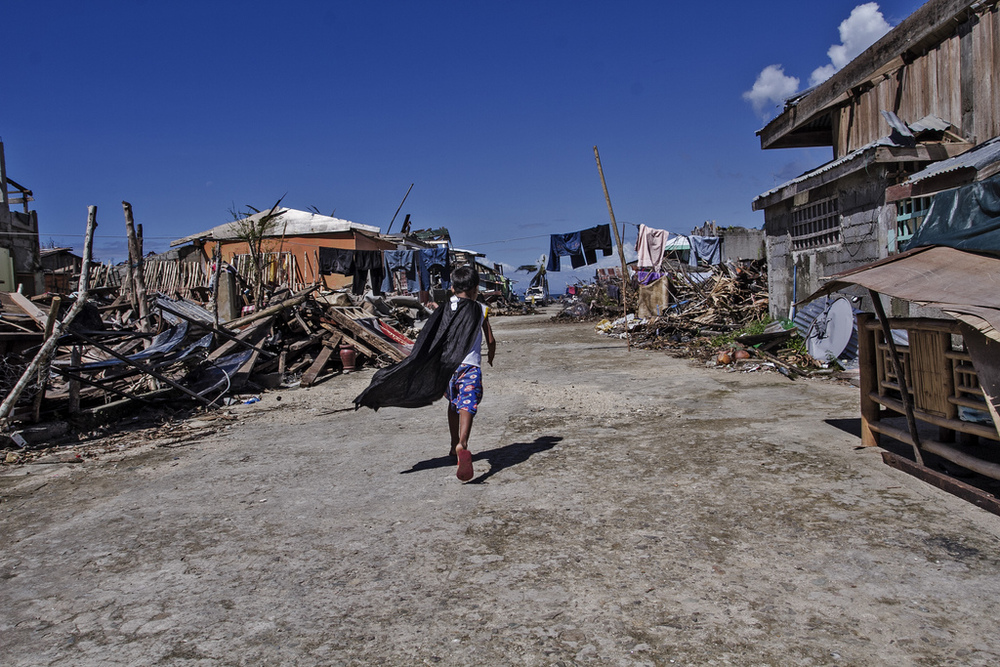 A caped boy runs between piles of wreckage in a street in Marabut City, Samar.
