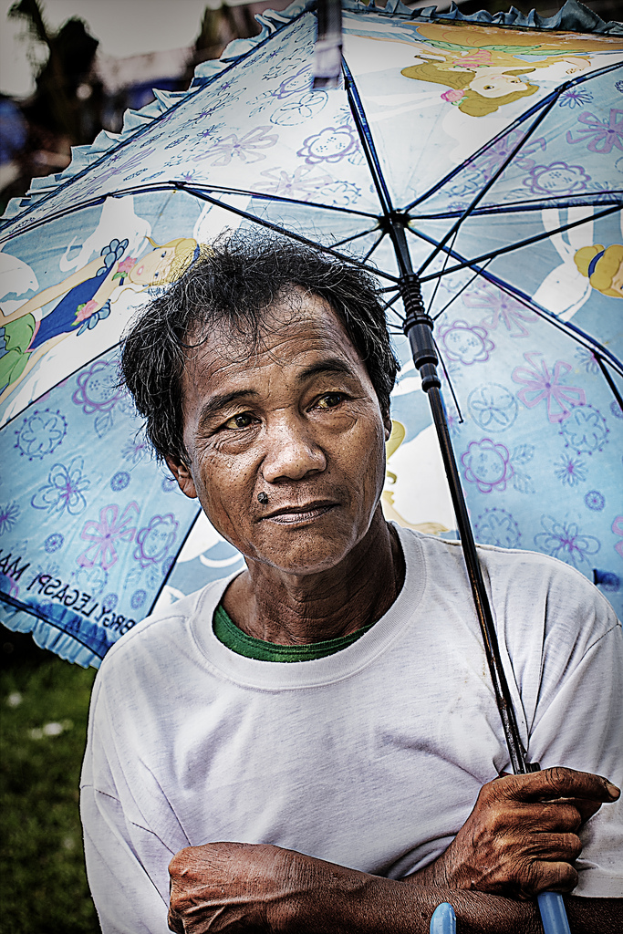 A man protects himself from the drizzle with a Disney princess umbrella. With means of livelihood largely destroyed, many men have little to do.
