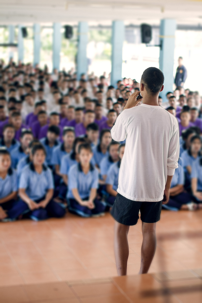 An inmate at the Mae Rim Juvenile Correction Facility is asked by officers to lead his peers in acapella song to welcome guests from the Sports Friends and Radical Grace teams in Chiang Mai, Thailand. To protect their privacy - and future prospects - we were asked not to publish the faces of any of the teens at the event.