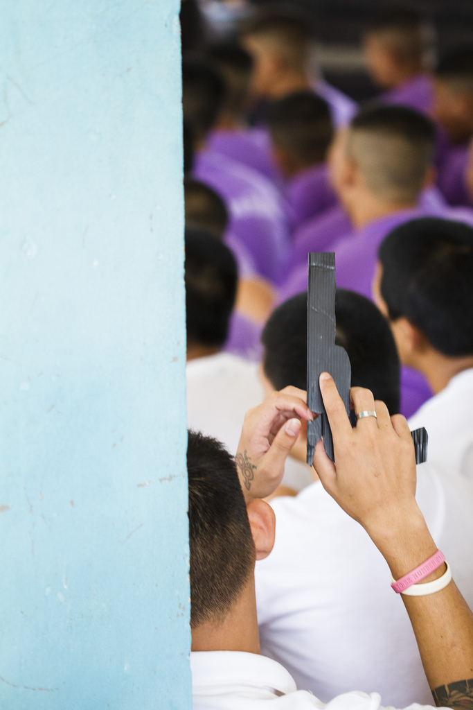 A young man at the Mae Rim Juvenile Correction Facility plays with a cardboard handgun as he listens to the combined team from Radical Grace and Sports Friends, Thailand talk about the importance of healthy relationships and good decision-making.