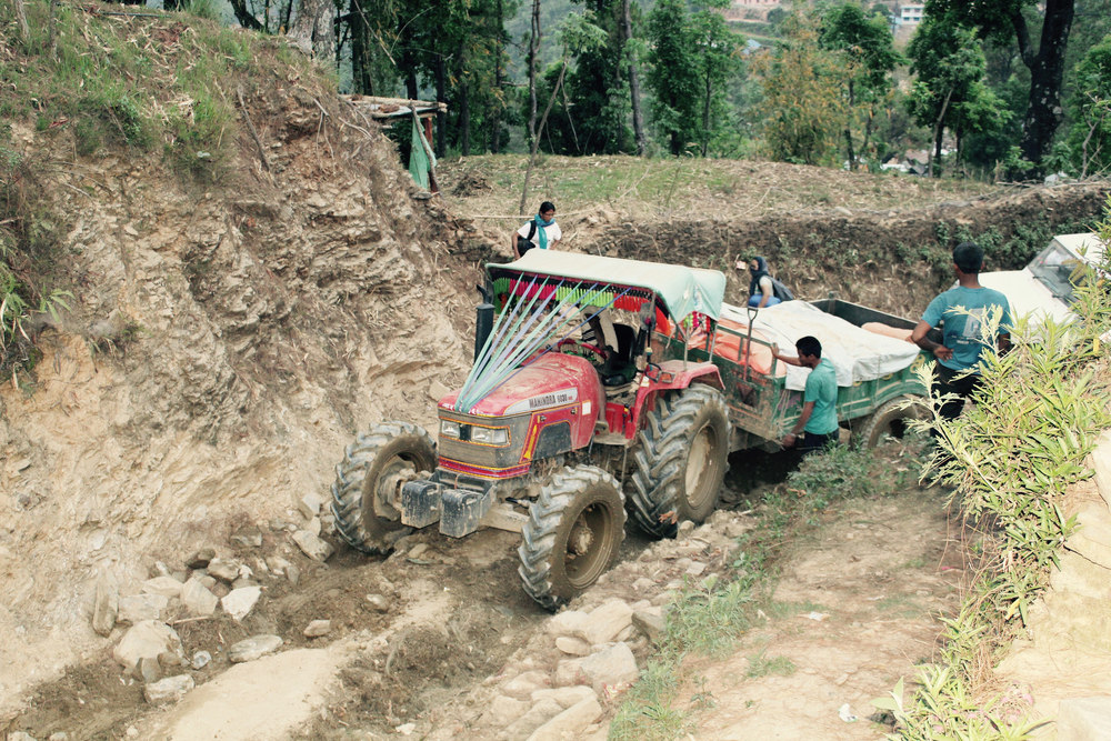 A UMN relief team guides a tractor towing relief supplies through a difficult mountain path. Photo courtesy of UMN.