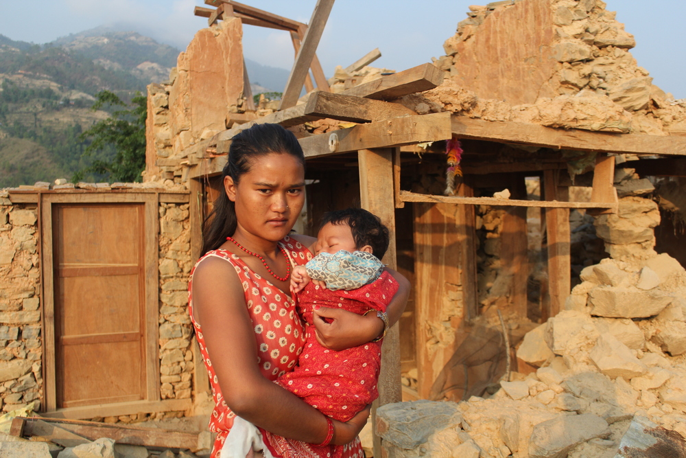 Suraj with his mother in front of the ruins of their house - Photo courtesy of UMN.