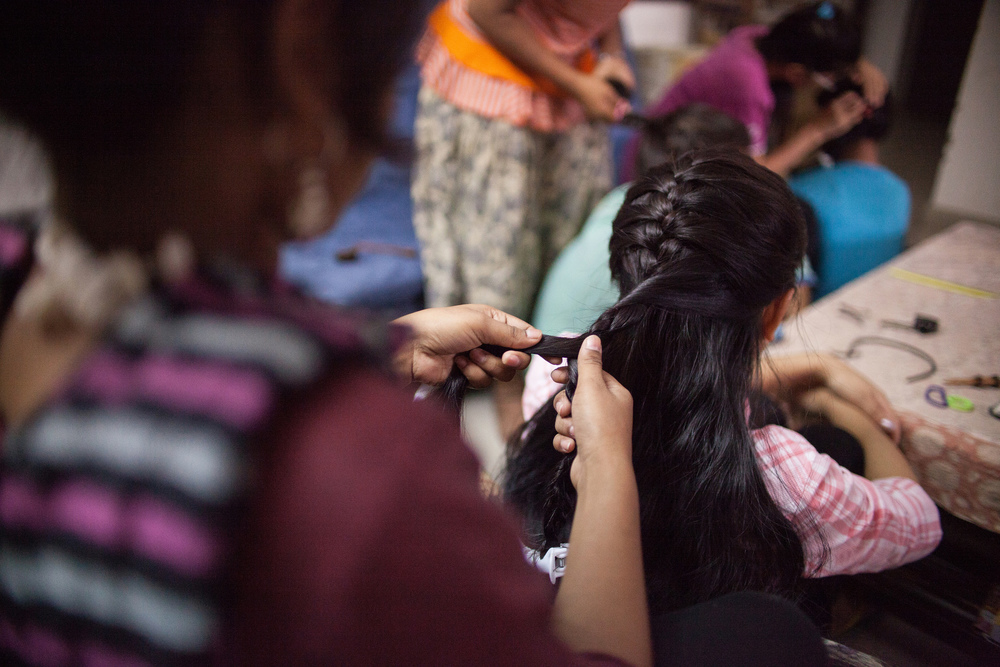 "The girls gather in a circle and braid each other's hair. This simple act of care underlies the deeper kinship in the home. ""I feel I am part of a family,"" Aarohi said."