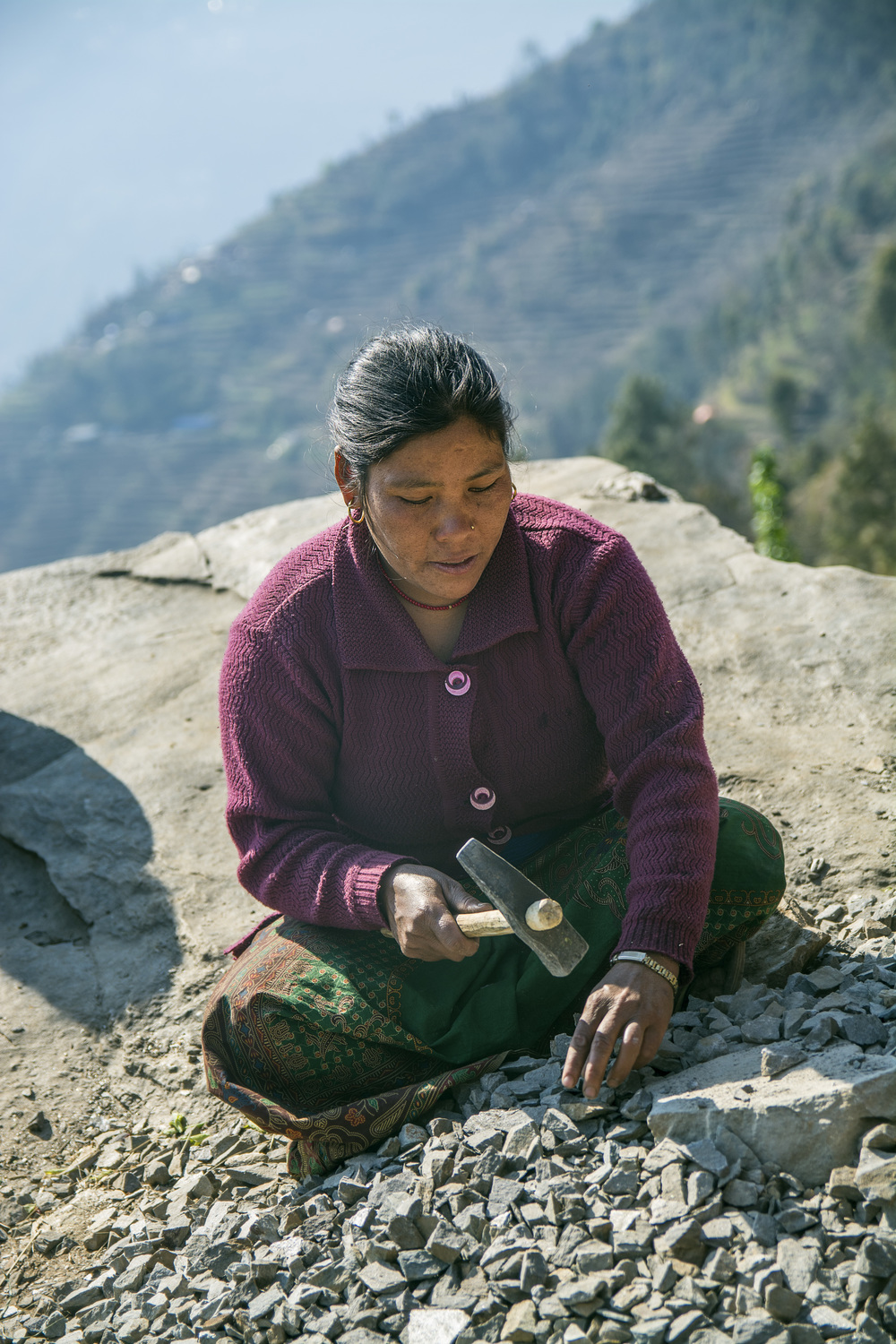 After Kalimaya Tamang spends the morning watering the new seeds in her family's fields and gets her daughter ready for school, she works to break stone to reconstruct the church building - photo by Mark Morrison.