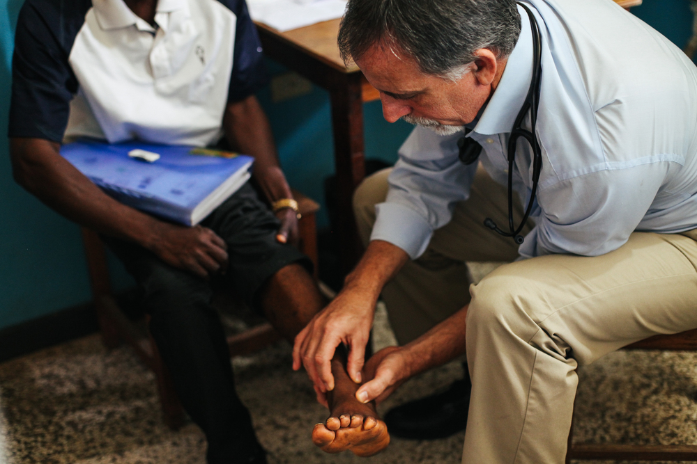 Dr. John Fankhauser examines an Ebola surivivor's ankle at ELWA Hospital. Survivors' symptoms can include debilitating joint pain. Dr. Fankhauser treated patients throughout the Ebola epidemic and now helps scores of survivors find relief for their Ebola complications - Photo by Bethany Fankhauser.