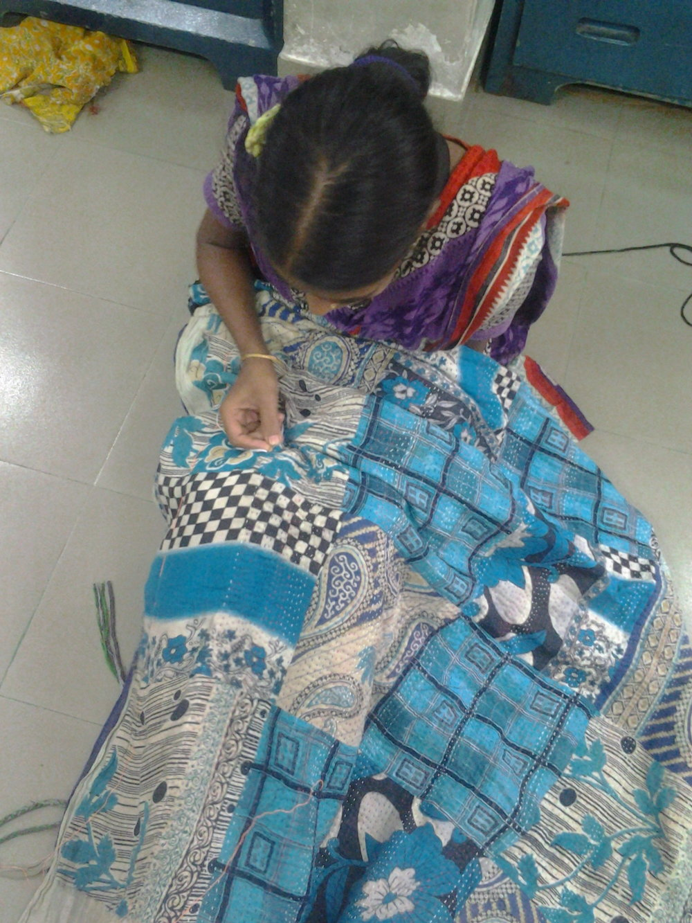A young woman works on a quilt as part of the vocational skills program in Dhaka - Photo by Edna.