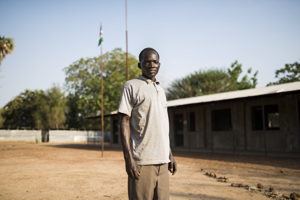 Graduate Wella Samuel stand outside the SIC Secondary School, which is now in Doro, South Sudan