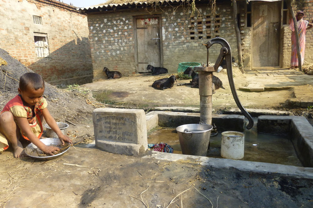 The local hand pump serves as the only running water for 15-20 village households. The simple concrete platform with drainage is a vital way to keep the area clean - Photo by Sarah K.