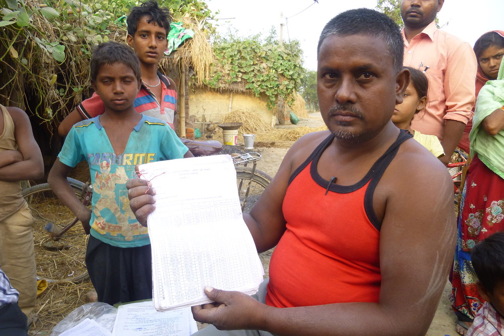 Serajul has paperwork for hundreds of villagers. He knows the situation of each person and can find peole's names and information with just a minute of searching - Photo by Sarah K.