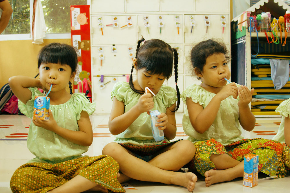 Girls enjoying a box of milk before Mary begins her English lesson for the day - Photo by Denise Poon.
