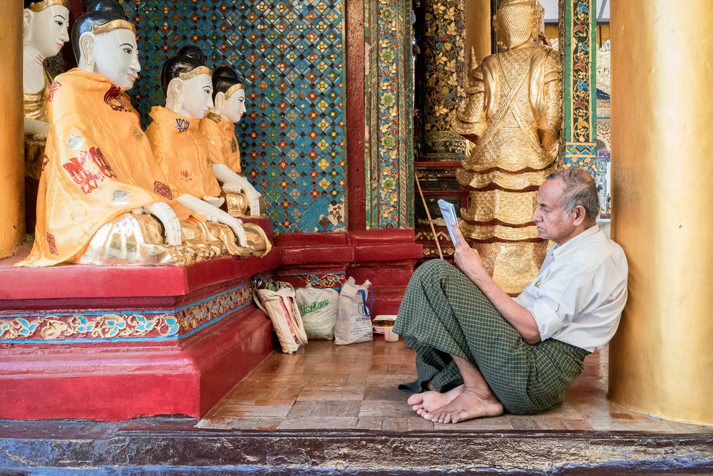 A man reads his newspaper at Shwedagon Pagoda, one of the biggest in Myanmar. Besides being tourist attractions pagodas are frequently community centres where people can buy food, meet others and relax - Photo by Denise Poon.
