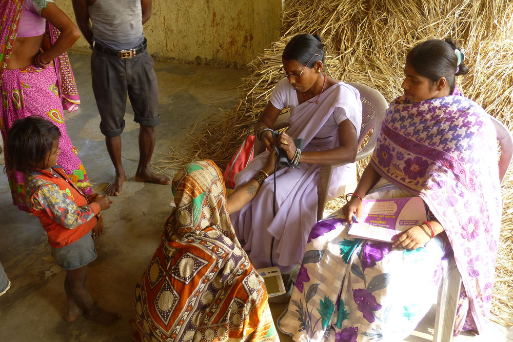 Khushboo (in the chair on the left) prepares to measure a local woman's blood pressure while other villagers watch with interest - photo by Sarah.