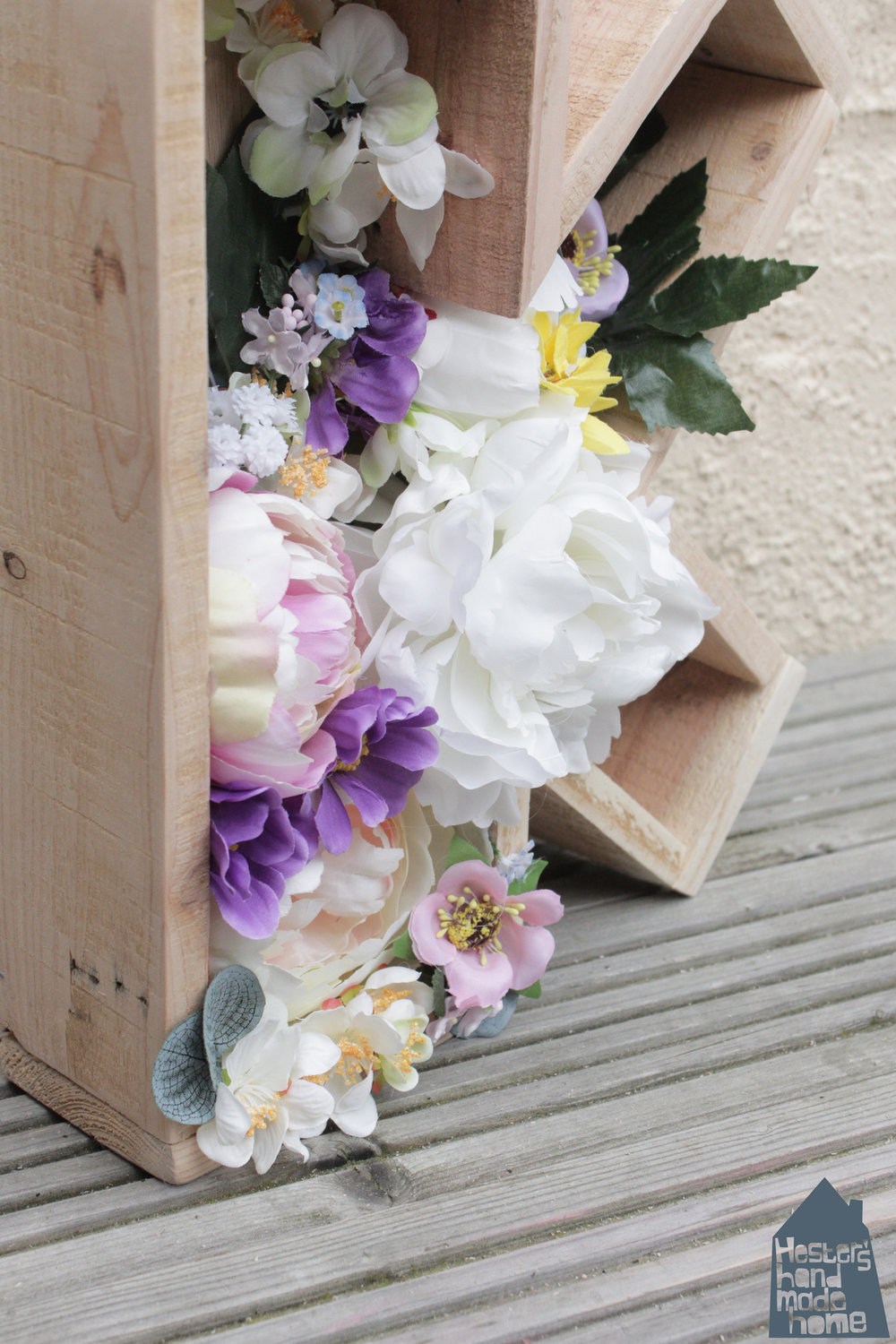 Pallet wood letter planter filled with faux flowers, tutorial by Hester's Handmade Home from her latest book Pallet Wood Projects for Outdoor Spaces