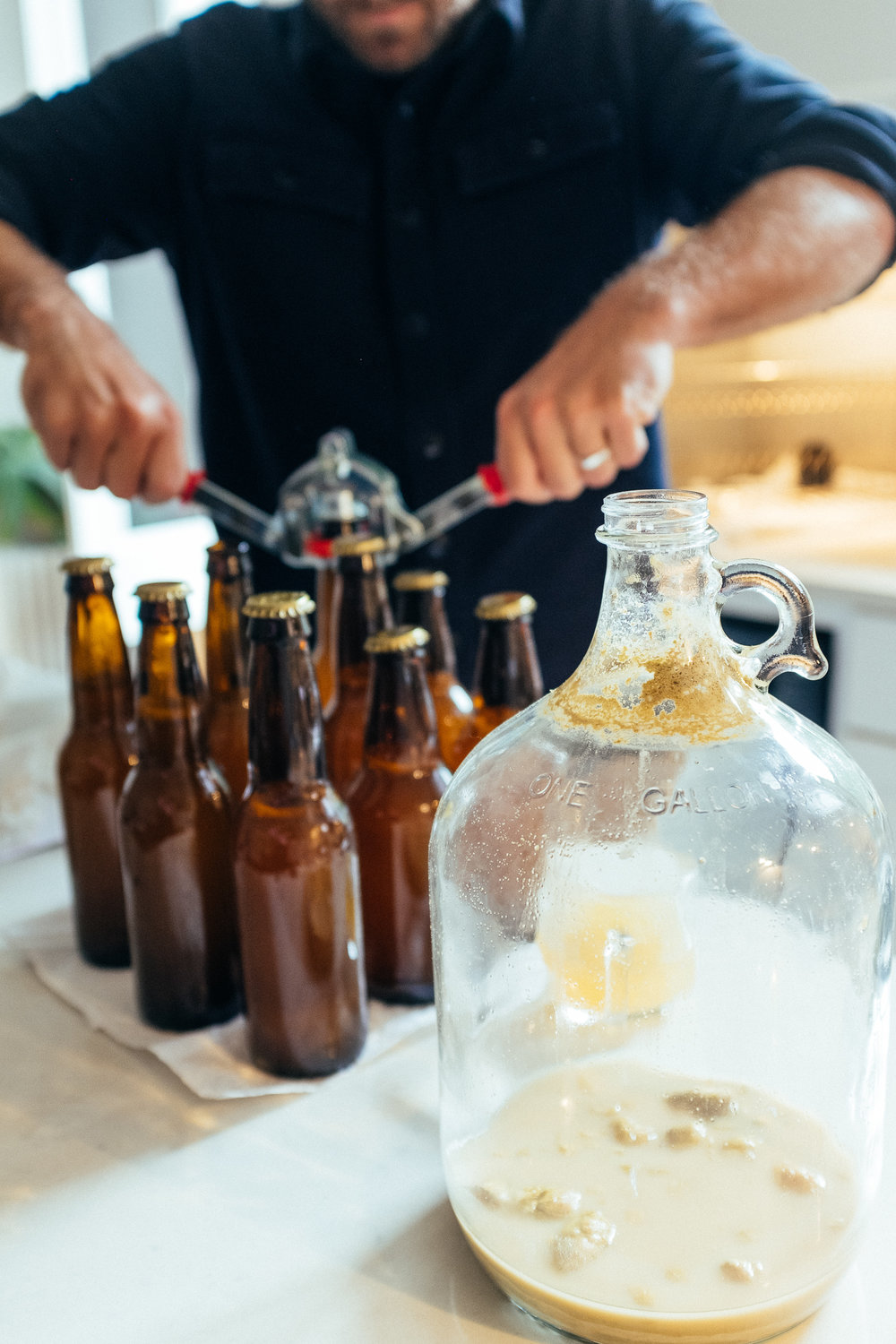 Having siphoned the beer out and added a small bit of honey, here I am bottling. The bottles wait for another two weeks for a second fermentation. This is when they get fizzy.